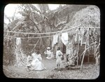 In this 1902 photo provided by York Museums Trust, residents are seen outside their home following explosive eruptions of La Soufrière volcano, in Chateaubelair, St. Vincent. Most of St. Vincent's casualties from the volcano in 1902 were in the east, possibly and partly because workers on large plantations were less able to make an independent decision to flee, according to Jenni Barclay, a volcanology professor. (Tempest Anderson/York Museums Trust via AP)