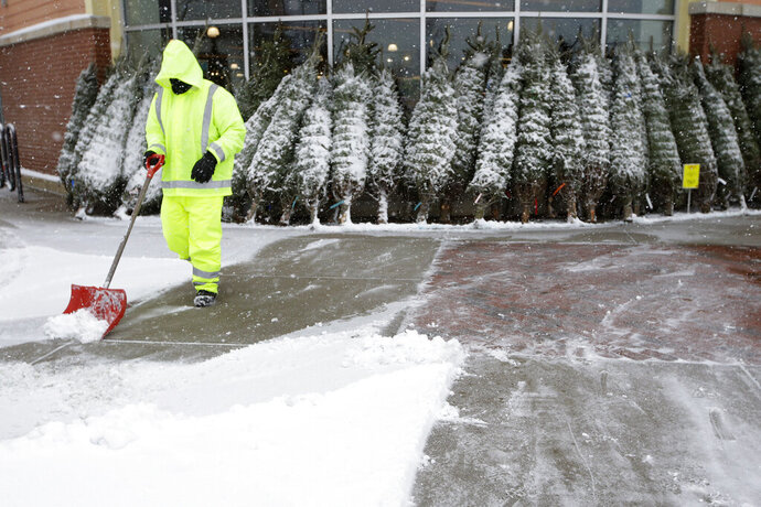 A worker shovels a sidewalk in front of a display of Christmas trees, Tuesday, Dec. 3, 2019, in Dedham, Mass. (AP Photo/Steven Senne)