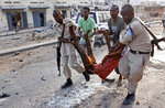 Somalis carry away an injured civilian who was wounded in a bomb blast near the Sahafi hotel in the capital Mogadishu, Somalia, Friday, Nov. 9, 2018. Three car bombs by Islamic extremists exploded outside the hotel, which is located across the street from the police Criminal Investigations Department, killing at least 10 people according to police. (AP Photo/Farah Abdi Warsameh)