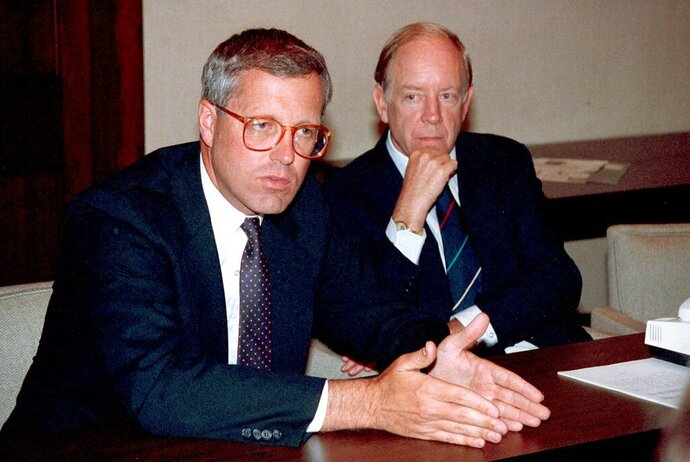 This Sept. 18, 1990 file photo shows James A. Johnson, left, after being elected by the board of directors to be the new chief executive officer of Fannie May succeeding David O. Maxwell, at right. Johnson, a former Democratic campaign operative who was CEO of housing lender Fannie Mae in the 1990s and served as chairman of Walter Mondale's presidential bid, died Sunday, Oct. 18, 2020 at his home in Washington. He was 76. (AP Photo/Doug Mills)