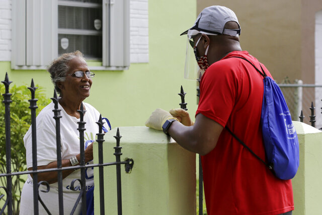 Morris Copeland, a team member of the Strategic Urban Response to Guideline Education (SURGE) group, right, talks with Louise Wilkerson, left, as he distributes kits to provide information to residents living in COVID-19 hotspots, during the new coronavirus pandemic, Wednesday, July 1, 2020, in the Liberty City neighborhood of Miami. The teams were formed by Miami-Dade County to help flatten the curve of the coronavirus. The kits contain masks, hand sanitizer, and information about testing locations. (AP Photo/Lynne Sladky)