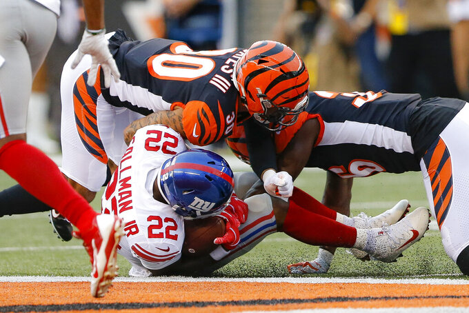 New York Giants running back Wayne Gallman (22) is tackled by Cincinnati Bengals free safety Jessie Bates (30) and defensive end Carlos Dunlap (96) during the first half of an NFL preseason football game, Thursday, Aug. 22, 2019, in Cincinnati. (AP Photo/Gary Landers)