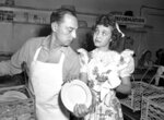 """FILE - In this April 22, 1944 file photo,  Jane Powell, who just completed work in """"Song of the Open Road"""" does her bit at the canteen drying dishes for dishwasher Buster Keaton, in Los Angeles. Jane Powell, the bright-eyed, operatic-voiced star of Hollywood's golden age musicals who sang with Howard Keel in """"Seven Brides for Seven Brothers"""" and danced with Fred Astaire in """"Royal Wedding,"""" has died. Thursday, Sept. 16, 2021. She was 92.  (AP Photo/File)"""