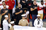 FILE - In this Sept. 1, 2016, file photo, San Francisco 49ers quarterback Colin Kaepernick, middle, kneels during the national anthem before an NFL preseason football game against the San Diego Chargers in San Diego. Kaepernick was a second-round draft pick in 2011 who the next year led the San Francisco 49ers to the Super Bowl. By 2016, he had begun kneeling on the sideline at games during the national anthem to protest social injustice and police brutality. Soon after, he was gone from the NFL, and he has not played since. (AP Photo/Chris Carlson, File)