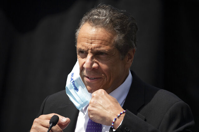 FILE - In this June 15, 2020, file photo, New York Gov. Andrew Cuomo removes a mask as he holds a news conference in Tarrytown, N.Y. On Wednesday, Aug. 26, 2020, the Justice Department sent letters to the governors of New York and three other Democratic-led states, seeking data on whether they violated federal law by ordering public nursing homes to accept recovering COVID-19 patients from hospitals, actions that have been criticized for potentially fueling the spread of the virus. (AP Photo/Mark Lennihan, File)