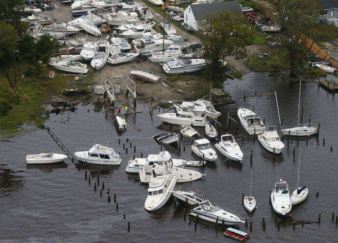 FILE - In this Sept. 15, 2018, file photo, boats are stacked up on each other in a marina as a following Hurricane Florence in New Bern, N.C. North Carolina Gov. Roy Cooper's office announced state and federal spending in response to Hurricane Florence has reached $1.9 billion, with an additional $921 million spent on recovery from 2016's Hurricane Matthew. (AP Photo/Steve Helber, File)