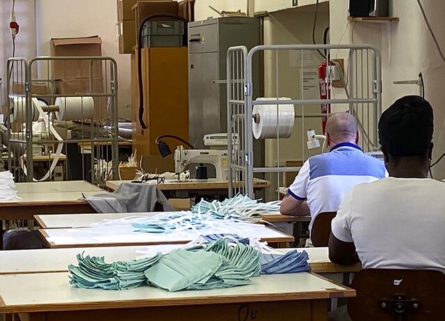 In this photo released by the Belgian Penitentiary Administration and made available on Monday, April 27, 2020, inmates sew face masks at the prison of Oudenaarde, Belgium. Inmates in Belgian prisons have made 42,000 reusable fabric masks to equip prison staff and prisoners amid a lack of protective equipment in the country. (Belgian Penitentiary Administration via AP)
