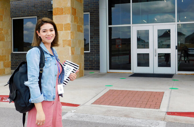 """First-year teacher Cindy Hipps stands outside of Lagos Elementary School, at Manor Independent School District campus east of Austin, Texas where she has taught first grade in a virtual and in-person hybrid classroom during the COVID-19 pandemic. Hipps said she was told she """"was introduced to the ring of fire of teaching."""" """"I feel like a superwoman now, like I can take on anything."""" (Acacia Coronado/Report for America via AP)"""