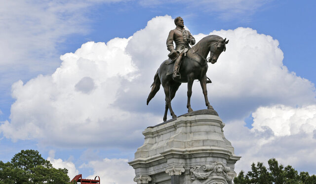 FILE - This June 27, 2017, file photo, shows the Confederate General Robert E. Lee statue that stands in the middle of a traffic circle on Monument Avenue in Richmond, Va. Newly empowered Virginia Democrats pledged Thursday, Jan. 9, 2020, to give local governments the ability to remove Confederate monuments, but Gov. Ralph Northam said he is still weighing what to do with perhaps the state's most prominent tribute to Gen. Robert E. Lee. (AP Photo/Steve Helber)