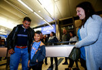 David Xol-Cholom, left, of Guatemala reunites with his son Byron, as Holly Sewell, right, sponsor mom to Bryon, looks on at Los Angeles International Airport after being separated about one and half year ago during the Trump administration's wide-scale separation of immigrant families, Wednesday, Jan. 22, 2020, in Los Angeles. (AP Photo/Ringo H.W. Chiu)