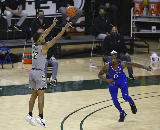 Baylor guard Jared Butler (12) shoots a three-point basket past Kansas guard Marcus Garrett (0) in the first half of an NCAA college basketball game, Monday, Jan. 18, 2021, in Waco, Texas. (AP Photo/Jerry Larson)