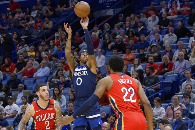 Minnesota Timberwolves guard D'Angelo Russell (0) shoots over New Orleans Pelicans forward Derrick Favors (22) during the first half of an NBA basketball game in New Orleans, Tuesday, March 3, 2020. (AP Photo/Matthew Hinton)