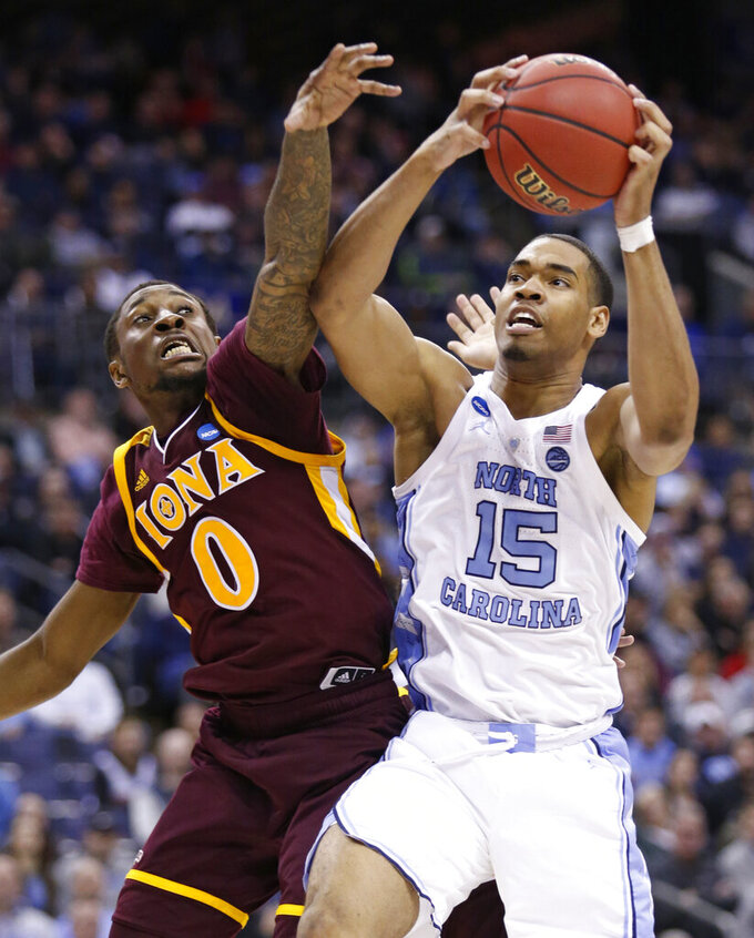 North Carolina's Garrison Brooks (15) drives to the basket against Iona's Rickey McGill (0) during the second half of a first-round game in the NCAA men's college basketball tournament in Columbus, Ohio, Friday, March 22, 2019. North Carolina won 88-73. (AP Photo/Paul Vernon)
