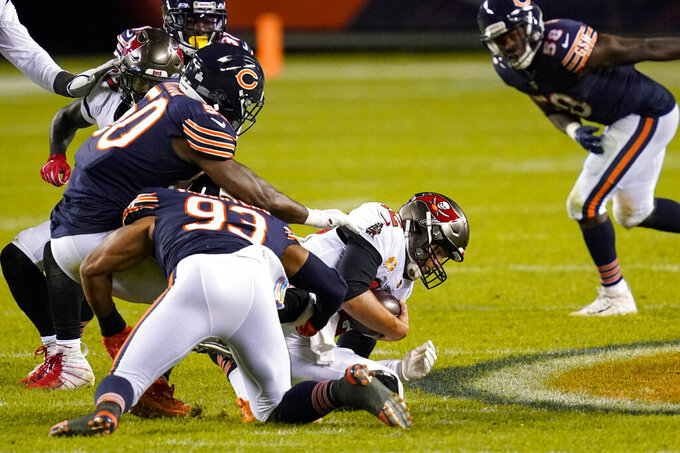 Tampa Bay Buccaneers quarterback Tom Brady (12) is sacked by Chicago Bears outside linebacker Barkevious Mingo (50) and linebacker James Vaughters (93) during the second half of an NFL football game in Chicago, Thursday, Oct. 8, 2020. (AP Photo/Charles Rex Arbogast)