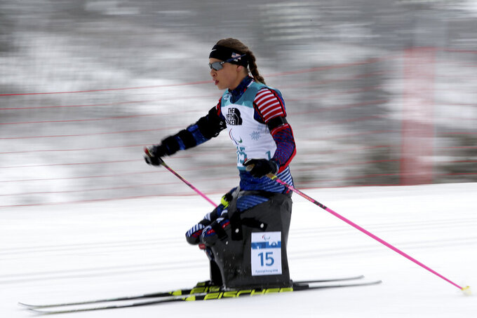 FILE - Oksana Masters, of the United States, on her way to a silver medal in the Biathlon Women's 12.5km Sitting event during the 2018 Winter Paralympics at the Alpensia Biathlon Centre in Pyeongchang, South Korea, March 16, 2018. Masters credits resiliency, determination and being headstrong for what she is today -- an eight-time Paralympic medalist. Masters persevered through 7 1/2 years in Ukrainian orphanages and with birth defects believed to be the aftermath of Chernobyl, the world's worst nuclear accident. That malnourished orphan eventually was adopted by her American mom. She will compete at the Paralympics in Tokyo in road cycling this week. In six months, she also plans to defend her cross-country skiing Paralympic titles in Beijing. (AP Photo/Ng Han Guan, file)
