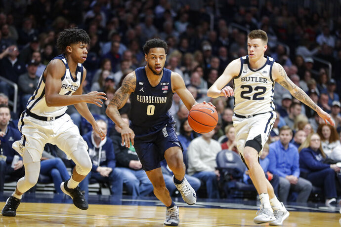 Georgetown guard Jahvon Blair (0) cuts between Butler guard Khalif Battle (4) and forward Sean McDermott (22) in the second half of an NCAA college basketball game in Indianapolis, Saturday, Feb. 15, 2020. Georgetown defeated Butler 73-66. (AP Photo/Michael Conroy)