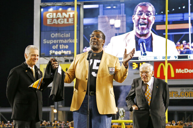 FILE - In this Nov. 2, 2014, file photo, Pittsburgh Steelers Pro Football Hall of Famer Joe Greene, center, makes remarks after receiving a jersey from Steelers President Art Rooney II, left, as Steelers chairman Dan Rooney, right, looks on during a ceremony to retire Greene's jersey number 75 at half time of an NFL football game between the Steelers and the Baltimore Ravens in Pittsburgh. The beginning of the Pittsburgh Steelers dynasty of the 1970s can be pinpointed to the drafting of defensive lineman Joe Greene in 1969. (AP Photo/Gene Puskar, File)