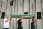 Bosnians carry the coffin of a victim outside the former UN base in Potocari, near Srebrenica, Bosnia, Friday, July 10, 2020. Nine newly found and identified men and boys will be laid to rest when Bosnians commemorate on Saturday 25 years since more than 8,000 Bosnian Muslims perished in 10 days of slaughter, after Srebrenica was overrun by Bosnian Serb forces during the closing months of the country's 1992-95 fratricidal war, in Europe's worst post-WWII massacre. (AP Photo/Kemal Softic)