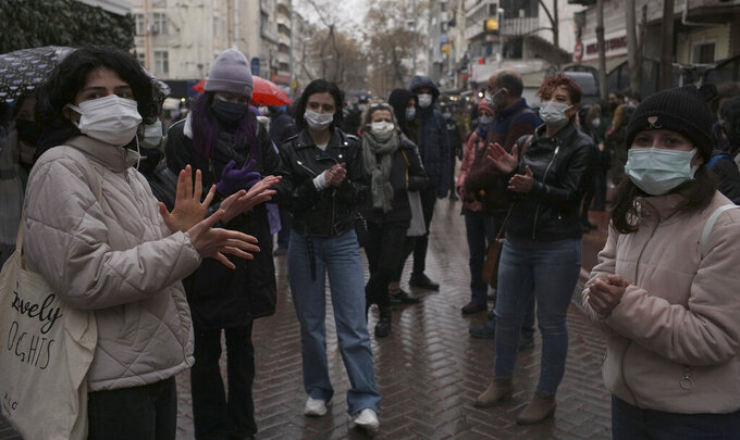 """Women wearing masks to protect against the spread of coronavirus, stand in the rain during a women's right protest, in Ankara, Turkey, Saturday, March 20, 2021. Turkey's weekly geographic COVID-19 figures keep increasing according to Health ministry statistics released late Saturday as the country continues its """"controlled normalization."""" (AP Photo/Burhan Ozbilici)"""