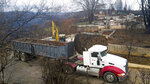 FILE - In this Feb. 8, 2019, file photo, an excavator loads debris onto a truck while clearing a property burned by the Camp Fire in Paradise, Calif. California officials said Tuesday, Nov. 19, 2019, that crews have finished removing millions of tons of debris left by a Northern California wildfire that killed 85 people and virtually annihilated a town. The Camp Fire, a year earlier, was the deadliest and most destructive wildfire in state history. (AP Photo/Noah Berger, File)