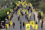 "FILE - In this June 8, 2018 file photo, Iraqi Popular Mobilization Forces march as they hold their flag and posters of Iraqi and Iranian Shiites spiritual leaders during ""al-Quds"" or Jerusalem Day, in Baghdad, Iraq. Iran-aligned Shiite militias are posing an increasing challenge for Iraq ahead of key talks with Washington in early April 2021, that are meant to shape the future of the U.S.-Iraq relationship. (AP Photo/Hadi Mizban, File)"