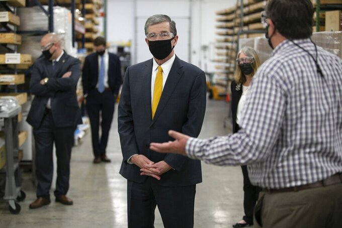 Bright View Technologies, director of operations Michael Bobay, gives North Carolina Governor Roy Copper a tour of the production facility where the company makes face shields on Thursday, Nov. 19, 2020 in Durham, N.C. Bright View Technologies produces optical management products and began producing face shields when the COVID-19 pandemic started.  (Robert Willett/The News & Observer via AP)