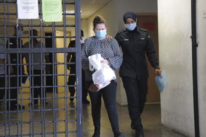 British woman Samantha Jones, left, leaves Alor Setar's courthouse, Kedah state, Malaysia, Monday, Aug. 3, 2020. Jones, accused of stabbing her husband to death at their Malaysian resort home avoided the gallows and was sentenced to 42 months in jail on Monday after she pleaded guilty to a lesser charge.  (AP Photo/Eric Tan)