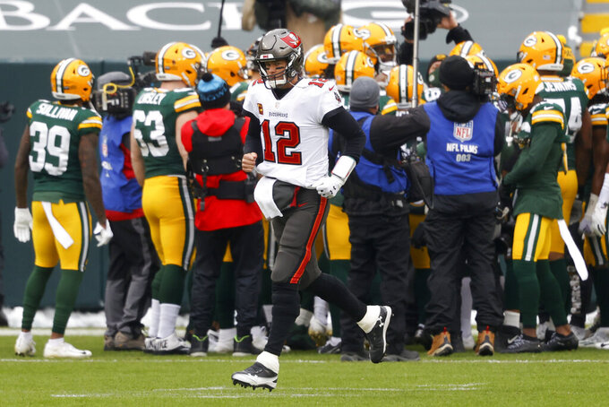 Tampa Bay Buccaneers quarterback Tom Brady (12) runs onto the field for warm ups before the NFC championship NFL football game against the Green Bay Packers in Green Bay, Wis., Sunday, Jan. 24, 2021. (AP Photo/Jeffrey Phelps)