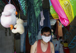Christopher Bagay, a kitchen crew of the Aida Sol cruise ship in Europe, walks beside children's toys upon arriving at his home in Laguna province, south of Manila, Philippines Thursday, May 28, 2020. Bagay said it took him about two months to go through repetitive quarantines in Spain, Germany and Manila before he was finally allowed to go home. Tens of thousands of workers have returned by plane and ships as the pandemic, lockdowns and economic downturns decimated jobs worldwide in a major blow to the Philippines, a leading source of global labor. (AP Photo/Aaron Favila)