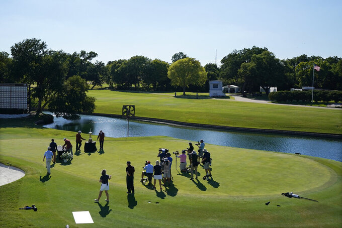 With no spectators in attendance, Daniel Berger is presented with the championship trophy in front of a small group of media after winning the Charles Schwab Challenge golf tournament after a playoff round at the Colonial Country Club in Fort Worth, Texas, Sunday, June 14, 2020. (AP Photo/David J. Phillip)