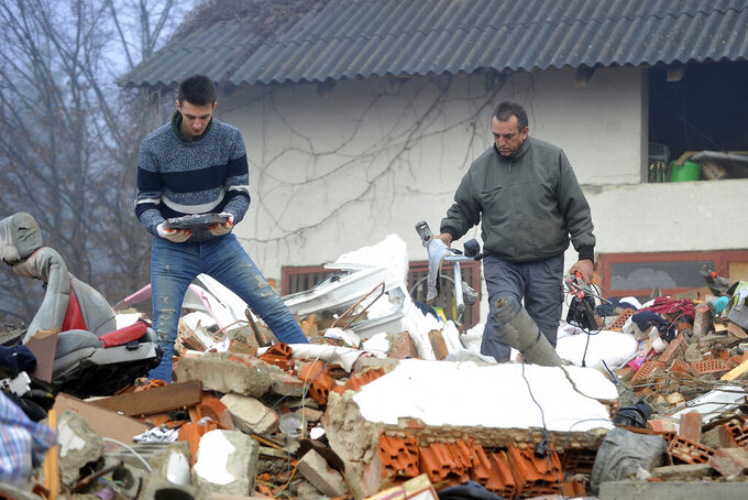 Men search through the rubble of collapsed houses in Majska Poljana, Croatia, Wednesday, Dec. 30, 2020. A series of tremors have jolted central Croatia a day after a 6.3-magnitude earthquake killed at least seven people, injured dozens and left several towns and villages in ruins. (AP Photo)