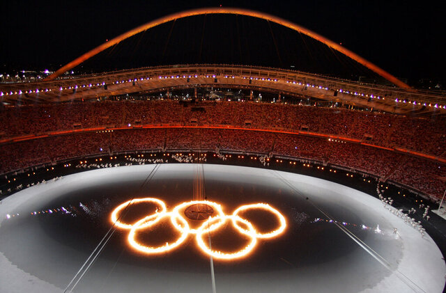 FILE - In this Aug. 13, 2004, file photo, the Olympic Rings are shown in flames in a pool of water during the Opening Ceremony of the 2004 Olympic Games in Athens. (AP Photo/Julie Jacobson, File)