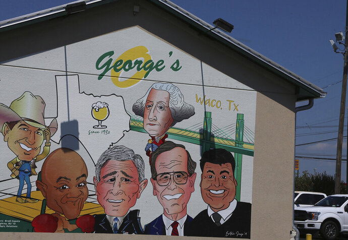 In this Aug. 17, 2019 photo, a Texas restaurant called George's that features a mural honoring famous men with the same name has been changed to avoid a trademark dispute. Owner Sammy Citrano discovered that an alphabet letter he'd put on the mural is a Waco city trademark, so it has now been changed to the historic suspension bridge. (Rod Aydelotte/Waco Tribune Herald via AP)