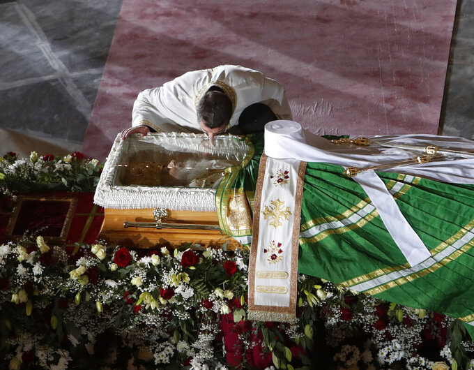 In this photo taken Saturday, Nov. 21, 2020, a priest kisses the coffin of Patriarch Irinej as he lies in repose at the St. Sava Temple in Belgrade, Serbia. After the two most senior Serbian Orthodox Church leaders died within a month after testing positive with the coronavirus, health experts and even hardcore believers are starting to worry. The spread of the virus within the largest religious group in the Balkans is getting more alarming by the day. (AP Photo/Darko Vojinovic)