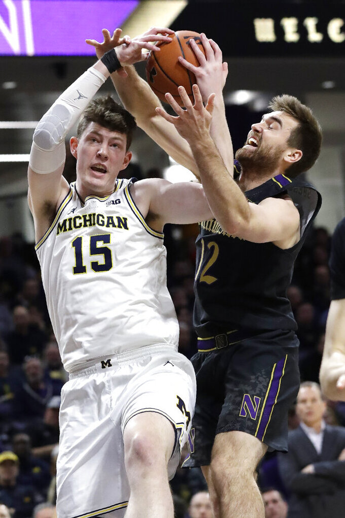 Michigan center Jon Teske, left, rebounds against Northwestern guard Pat Spencer during the first half of an NCAA college basketball game in Evanston, Ill., Wednesday, Feb. 12, 2020. (AP Photo/Nam Y. Huh)