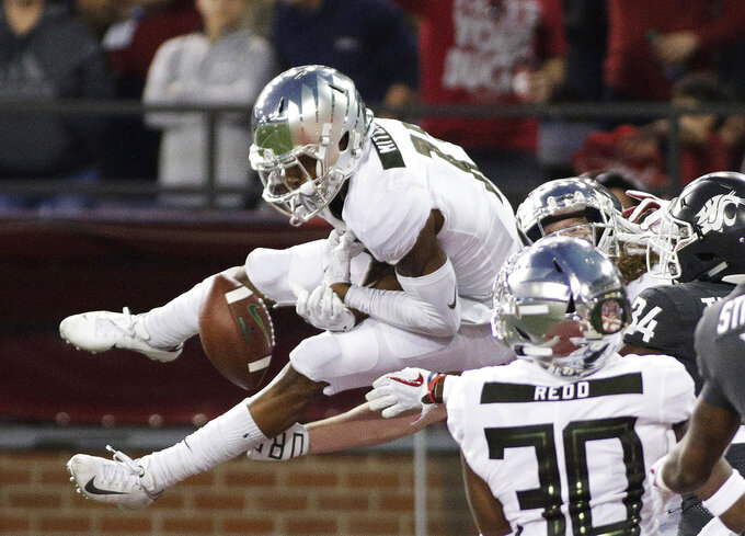 Oregon wide receiver Dillon Mitchell, left, can't hold onto a pass in the end zone at the end of the first half of an NCAA college football game against Washington State in Pullman, Wash., Saturday, Oct. 20, 2018. (AP Photo/Young Kwak)