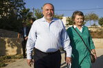 FILE - In this Tuesday, Sept. 17, 2019 file photo, leader of the Yisrael Beiteinu right-wing nationalist party Avigdor Liberman arrives to vote with is wife Ella in the settlement of Nokdim, West Bank. In Israel's secular heartland, the role of religion in daily life played a central role in this week's deadlocked election. Lieberman positioned himself as the primary power broker by making it his signature cause and defecting from Netanyahu's camp over what he called its capitulation to the ultra-Orthodox.  (AP Photo/Tsafrir Abayov, File)