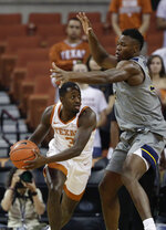 Texas guard Courtney Ramey (3) is pressured by West Virginia forward Oscar Tshiebwe (34) during the first half of an NCAA college basketball game, Monday, Feb. 24, 2020, in Austin, Texas. (AP Photo/Eric Gay)