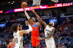 Oklahoma City Thunder guard Shai Gilgeous-Alexander (2) drives to the basket between New Orleans Pelicans center Jaxson Hayes (10) and forward Brandon Ingram (14) in the first half of an NBA basketball game in New Orleans, Sunday, Dec. 1, 2019. (AP Photo/Gerald Herbert)