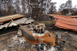 A lawn mower is barely recognizable after a fire destroyed a home at Nerrigundah, Australia, Monday, Jan. 13, 2020, after a wildfire ripped through the town on New Year's Eve. The tiny village of Nerrigundah in New South Wales has been among the hardest hit by Australia's devastating wildfires, with about two thirds of the homes destroyed and a 71-year-old man killed. (AP Photo/Rick Rycroft)