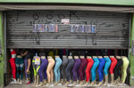 A store worker opens a clothing shop in a downtown shopping district of Sao Paulo, Brazil, Wednesday, June 10, 2020. Retail shops reopened on Wednesday in Brazil's biggest city after a two-month coronavirus pandemic shutdown that aimed to contain the spread of the new coronavirus. (AP Photo/Andre Penner)
