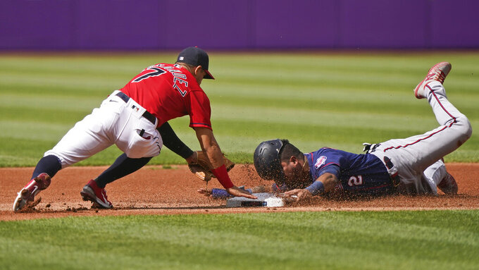 Minnesota Twins' Luis Arraez, right, tries to steal to second base as Cleveland Indians' Cesar Hernandez, left, makes the tag in the first inning of a baseball game, Saturday, May 22, 2021, in Cleveland. (AP Photo/Tony Dejak)