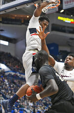 Connecticut's Alterique Gilbert, top, and Eric Cobb, right, defend against Central Florida's Tacko Fall during the first half of an NCAA college basketball game, Saturday, Jan. 5, 2019, in Hartford, Conn. (AP Photo/Jessica Hill)