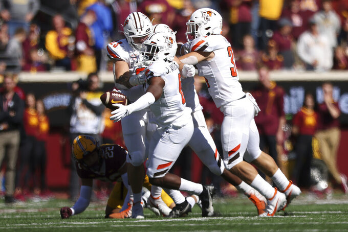 Bowling Green safety Jordan Anderson (0) is surrounded by teammates in celebration after intercepting the ball during the second half of an NCAA college football game against Minnesota, Saturday, Sept. 25, 2021, in Minneapolis. Bowling Green won 14-10. (AP Photo/Stacy Bengs)