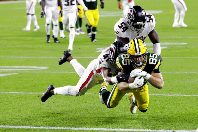 Robert Tonyan de los Packers de Green Bay consigue un touchdown mientras es tacleado por Sharrod Neasman de los Falcons de Atlanta en la primera mitad del juego del lunes 5 de octubre de 2020, en Green Bay, Wisconsin. (AP Foto/Mike Roemer)