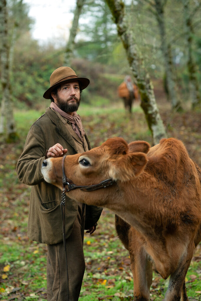 """This image released by A24 shows John Magaro in a scene from the film """"First Cow.""""  The film was nominated for best feature by the Independent Film Spirit Awards. (Allyson Riggs/A24 via AP)"""