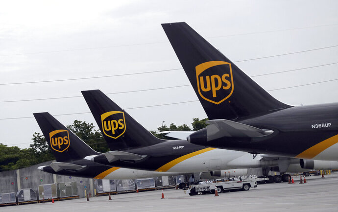 In this July 27, 2020 file photo, the tails of three UPS aircraft are shown parked at Miami International Airport in Miami. UPS, whose brown delivery trucks have become omnipresent on neighborhood streets during the pandemic, is reporting strong profits and revenue in its most recent quarter.  (AP Photo/Wilfredo Lee, File)
