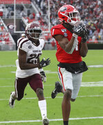 Georgia wide receiver George Pickens (1) makes a catch for a touchdown as Texas A&M defensive back Debione Renfro (29) defends in the first half of an NCAA college football game Saturday, Nov. 23, 2019, in Athens, Ga. (Curtis Compton/Atlanta Journal-Constitution via AP)