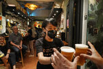 In this Oct. 9, 2020 photo, a bartender serves beers at Club 71 in Central, a business district of Hong Kong. The bar known as a gathering place for pro-democracy activists and intellectuals is closing. (AP Photo/Kin Cheung)