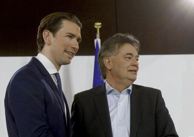 Sebastian Kurz, left, head of the Austrian People's Party, OEVP, poses with Werner Kogler, right, head of the Austrian Greens after a press conference about the government program in Vienna, Austria, Thursday, Jan. 2, 2020. (AP Photo/Ronald Zak)